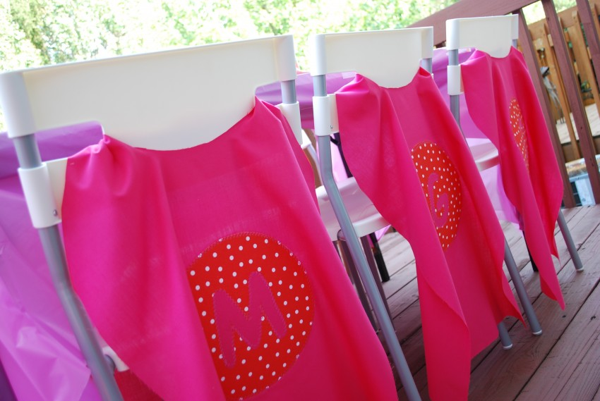 Girl's superhero birthday party - monogrammed capes on chair backs
