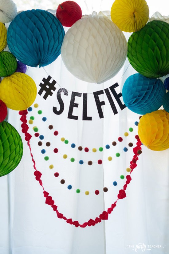Selfie Scavenger Hunt Birthday Party by The Party Teacher - Photo booth with honeycomb balls and garlands
